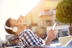 Jeune homme écoutant la musique à un téléphone intelligent Image libre de droits