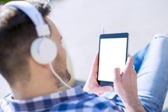 Jeune homme écoutant la musique à un téléphone intelligent Photographie stock