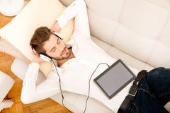 Jeune homme écoutant la musique Photographie stock