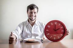 Jeune homme élégant avec la chemise blanche tenant l'horloge rouge image libre de droits