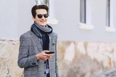Jeune homme élégant dans des lunettes de soleil avec le téléphone sur la rue photographie stock libre de droits