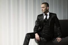 Jeune homme élégant de mode dans le smoking se reposant sur un sofa Image libre de droits