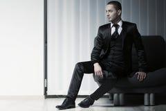 Jeune homme élégant de mode dans le smoking sur un sofa, fond d'abat-jour Photographie stock libre de droits