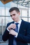 Jeune homme élégant de mode regardant ses boutons de manchette tout en les fixant images libres de droits