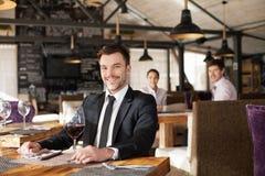Jeune homme élégant s'asseyant dans le restaurant Photographie stock
