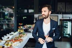 Jeune homme élégant se tenant dans le restaurant, tenant un verre de vin Le type de l'homme Images stock