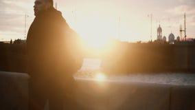 Jeune homme élégant se tenant sur le remblai près de la rivière et appréciant la belle vue sur le coucher du soleil Mâle marchant banque de vidéos