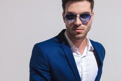 Jeune homme élégant sexy dans le costume et des lunettes de soleil bleus photos libres de droits