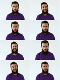 Jeune homme émotif avec une barbe et une chemise pourpre regardant l'appareil-photo dans un studio sur un fond blanc Portrait Photo stock