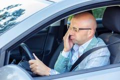 Jeune homme épuisé de baîllement fatigué somnolent conduisant sa voiture image libre de droits