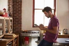 Jeune homme épuisant la tablette dans la cuisine, taille Image libre de droits