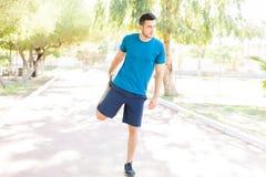 Jeune homme étirant la jambe avant la formation de forme physique en parc photos libres de droits