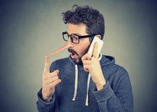 Jeune homme étonné avec le long nez parlant au téléphone portable image libre de droits