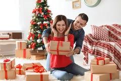Jeune homme étonnant son amie avec le cadeau de Noël Photo stock