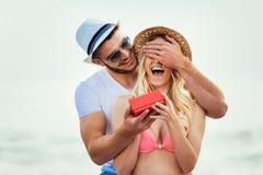 Jeune homme étonnant son amie avec le cadeau sur la plage Photo stock