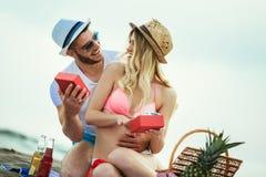 Jeune homme étonnant son amie avec le cadeau sur la plage Photo libre de droits