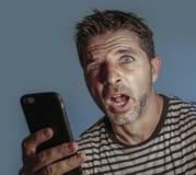 Jeune homme étrange et fol d'intoxiqué de téléphone portable utilisant la cellule compulsif avec l'expression étrange et anormale photo libre de droits