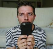 Jeune homme étrange et fol d'intoxiqué de téléphone portable utilisant la cellule compulsif avec l'expression étrange et anormale images libres de droits
