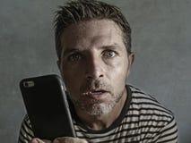 Jeune homme étrange et fol d'intoxiqué de téléphone portable utilisant la cellule compulsif avec l'expression étrange et anormale image libre de droits