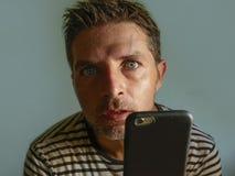 Jeune homme étrange et fol d'intoxiqué de téléphone portable utilisant la cellule compulsif avec l'expression étrange et anormale photographie stock