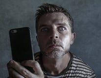 Jeune homme étrange et fol d'intoxiqué de téléphone portable utilisant la cellule compulsif avec l'expression étrange et anormale photos stock