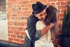 Jeune homme étreignant une femme dans un café Photos stock