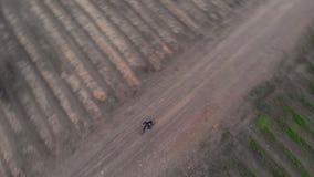 Jeune homme aérien de tir faisant un cycle sur la bicyclette à la route rurale par des terres cultivables banque de vidéos