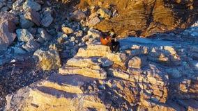 Jeune homme aérien et seul jouant la guitare se reposant sur une roche côtière clips vidéos