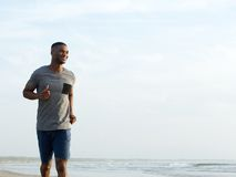 Jeune homme actif pulsant à la plage Image libre de droits
