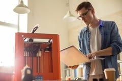 Jeune homme actionnant l'imprimante 3D Photographie stock