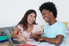 Jeune homme adulte d'afro-américain apprenant avec le girlfri caucasien Photographie stock