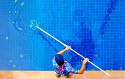 Jeune homme adulte, personnel nettoyant la piscine des feuilles Images libres de droits