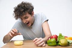Jeune homme affamé s'asseyant à la table Images stock