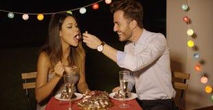 Jeune homme affectueux alimentant son gâteau d'amie Photographie stock libre de droits