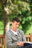 Jeune homme affichant son livre sur le banc Photos libres de droits