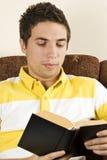 Jeune homme affichant un livre Image stock
