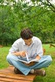 Jeune homme affichant un livre en stationnement Images stock