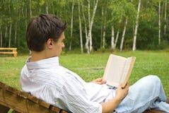 Jeune homme affichant un livre en stationnement Photographie stock libre de droits
