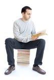 Jeune homme affichant un livre sur le fond blanc Photo libre de droits