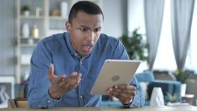 Jeune homme africain contrarié pour la perte tout en à l'aide de la Tablette photo stock