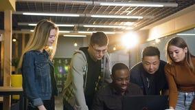 Jeune homme africain d'affaires travaillant à l'ordinateur portable dans le bureau moderne tandis que groupe de jeune cowoker ven banque de vidéos