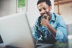 Jeune homme africain de sourire faisant l'appel visuel avec des amis tout en se reposant sur le sofa à son bureau moderne Concept Image libre de droits