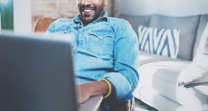 Jeune homme africain de sourire faisant la conversation visuelle avec des amis tout en se reposant sur le sofa à sa maison ensole Image libre de droits