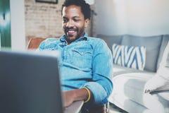 Jeune homme africain de sourire faisant la conversation visuelle avec des amis tout en se reposant sur le sofa à sa maison ensole Image stock