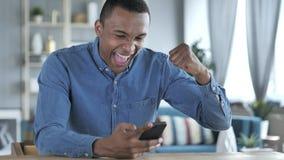 Jeune homme africain excité pour le succès tout en employant Smartphone photographie stock libre de droits