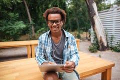Jeune homme africain gai à l'aide du comprimé et souriant dans le parc Image stock