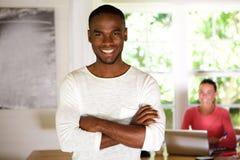 Jeune homme africain heureux se tenant avec ses bras croisés photo libre de droits