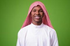 Jeune homme africain portant les vêtements musulmans traditionnels contre le gre photos libres de droits