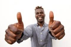 Jeune homme africain positif souriant avec deux pouces  Photos stock