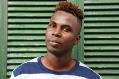 Jeune homme africain positif souriant avec deux pouces  Photographie stock libre de droits